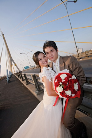 road of love: couples of happiness Bride and groom with beautiful rose bouquet on the road bridge
