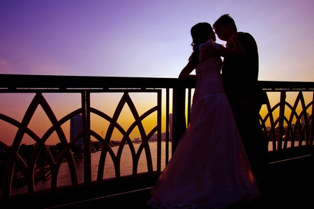 shilhouette of romantic and happiness couples on the bridge over the river photo