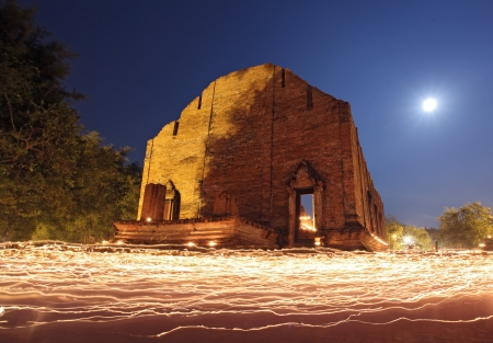 candle light trail of Buddhism Ceremony at temple ruin with moon on Asalha Puja Day photo
