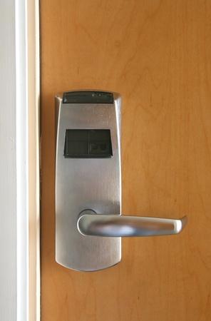 Keycard electronic lock on closed wooden door photo