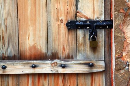 Old iron metal door handle locker on vintage italian style wooden door photo