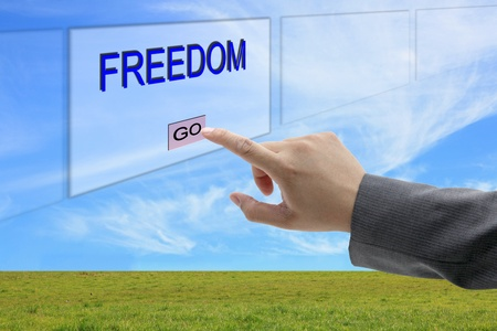 key to freedom: asian business man hand push on Freedom button on touch screen panel Stock Photo