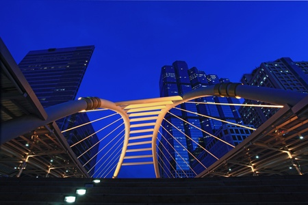 Bangkok pubic skywalk in business district downtown cityscape at night photo