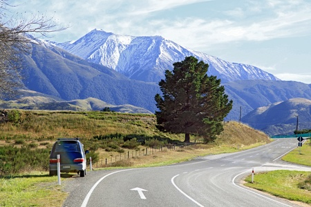 Long winding road stretching out into the distance with snow mountain background in New Zealand photo