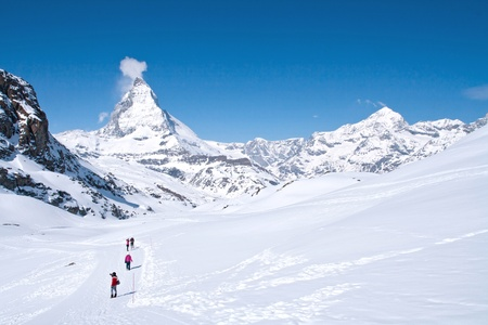 traditional climbing: traveler hiking to Matterhorn alpine alps range Switzerland Stock Photo