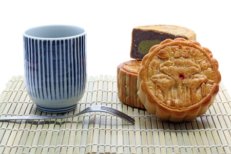 set of moon cake and tea with fork on bamboo dish photo