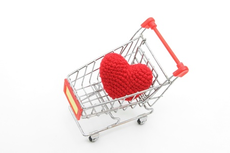 prostitution: love delivery concept, red heart in Shopping cart isolated on white