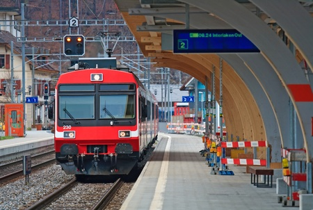 railroad station platform: Red Train coming to Interlaken Station Switzerland