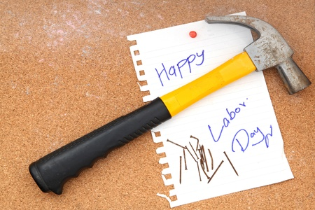 hammer and rusty nails with paper attach to cork board for labor day photo
