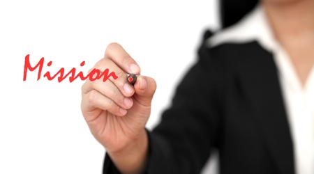 vision concept: asian business woman hand writing Mission word