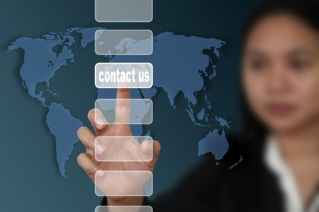 email contact: female hand touch on contact us button with world map background