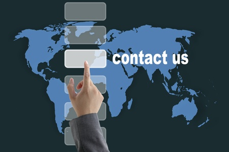 email contact: male business hand pushing on contact us button with world map background Stock Photo