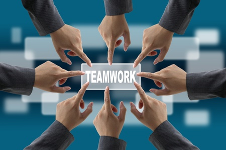 agree: A diverse business team with hands together push teamwork button Stock Photo