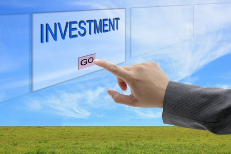 asian business man hand push on Investment button on touch screen panel Stock Photo - 10888581