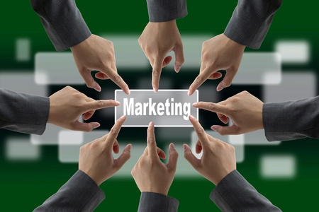 consensus: A diverse business team with hands together push Green Marketing button Stock Photo