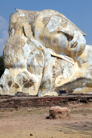 giant reclining buddha statue over blue sky at temple ruin photo