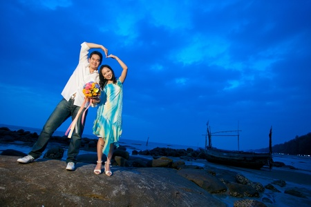 young couples making heart sign at the beach photo