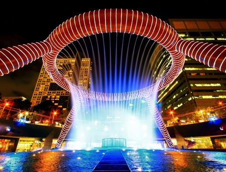 Singapore JAN 22: Fountain of Wealth with Suntec Towers at dusk on JAN 22,2010 in Singapore. Fountain of wealth is the biggest fountain in Singapore located Suntec Towers on Marina Bay.
