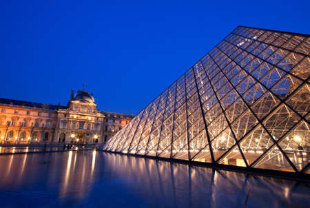 PARIS - APRIL 16: Closeup of Louvre Pyramid shined at dusk on April 16, 2010 in Paris. Louvre is the biggest Museum in Paris displayed over 60,000 square meters of exhibition space. Stock Photo - 11249904