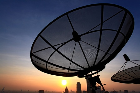 remote communication: black antenna communication satellite dish over sunset sky in cityscape