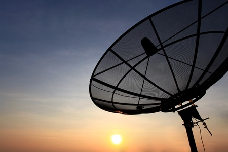 black antenna communication satellite dish over sunset sky in cityscape photo