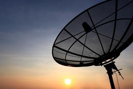 black antenna communication satellite dish over sunset sky in cityscape photo