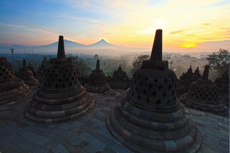 java: Sunrise at Ancient stupa Borobudur Temple, with Mount Merapi Background in Yogyakarta, Java, Indonesia.
