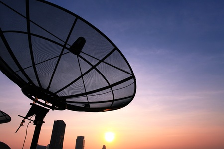 remote access: black antenna communication satellite dish over sunset sky in cityscape