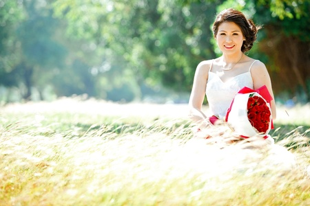 portrait of beautiful bride with rose bouquet on meadows field photo