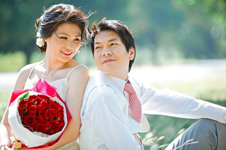 portrait of bride and groom making eye contact with rose bouquet photo