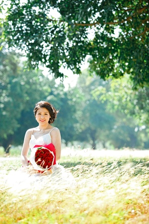 portrait of beautiful bride with rose bouquet on autumn meadows field Stock Photo - 11772291