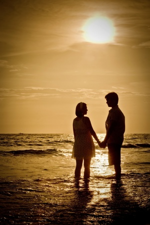 aniversary: romantic Scene of couples on the Beach with sunset
