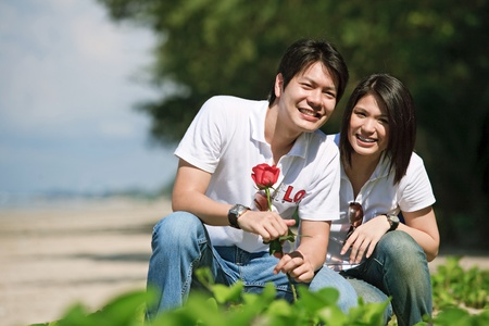 boy giving beautiful rose to his pretty girlfriend photo