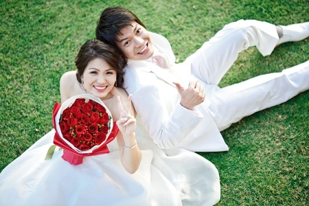 portrait of bride and groom sitting on fresh grass with rose bouquet photo