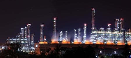 panoramic view of oil refinery factory shines at night photo