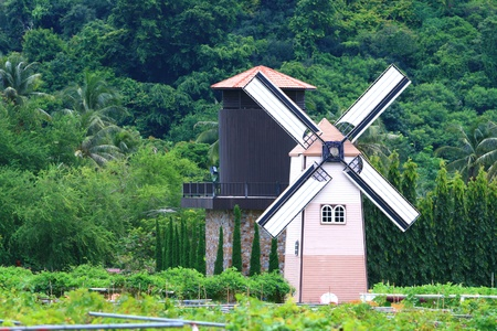 Traditional Old dutch windmill in Thailand with Agriculture Silo photo