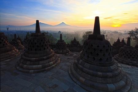 yogyakarta: Sunrise at Ancient stupa Borobudur Temple, with Mount Merapi Background in Yogyakarta, Java, Indonesia.