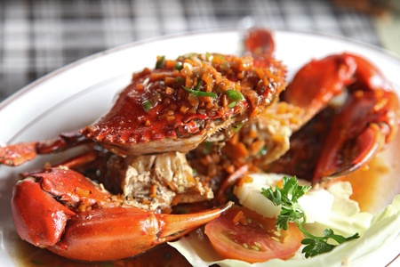 crabs: cooked crabs with spicy sauce on white plate (selective focus) Stock Photo