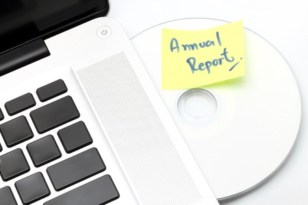 writable: White laptop with Business Annual Report dvd disk in slot-loading drive on a white background. Stock Photo