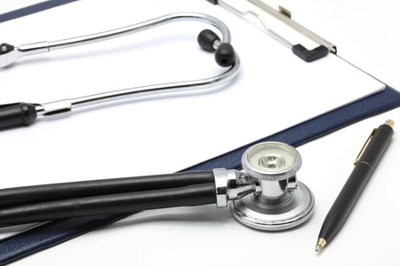 A clipboard with Blank Paper Pad with a stethoscope and Pen on white background (delective focus at Stethoscope) photo