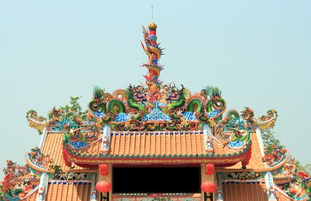 Dragon Statue on Top of Chinese Temple Shrine with blue sky photo