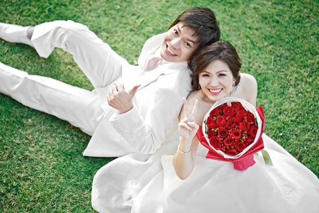 portrait of bride and groom sitting on fresh grass with rose bouquet Stock Photo - 12331836