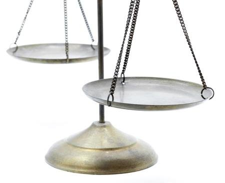 balanza en equilibrio: punto de vista de las escalas de latón dorado de la justicia en el fondo blanco