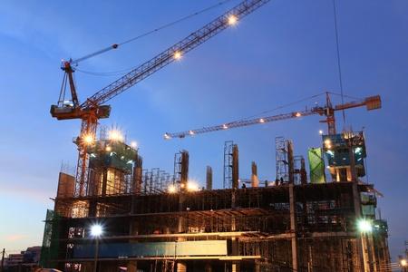 cantieri edili: Ponteggi cantiere al crepuscolo con gru in movimento