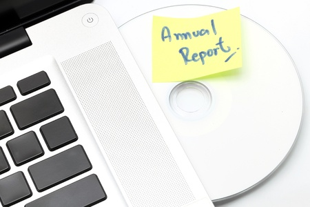 White laptop with Business Annual Report dvd disk in slot-loading drive on a white background. photo