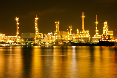 Oil refinery plant shines at night along river