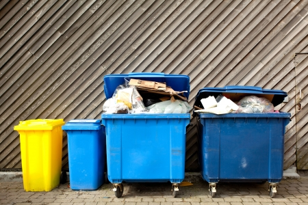 waste management: overfilled trash of large wheelie bins for rubbish, recycling and garden waste Stock Photo