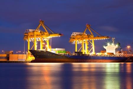 szállítás: Konténer Cargo áruszállító hajó működő daru híd hajógyár alkonyatkor logisztikai Import Export háttér