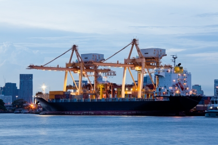 Container Cargo freight ship with working crane bridge in shipyard at evening for Logistic Import Export background Stock Photo - 14136331