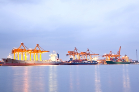 Big Container Cargo freight ship with working crane in shipyard at night for Logistic Import Export background photo